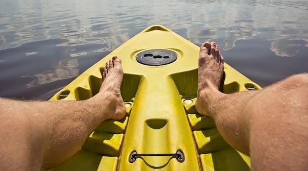 El hombre nada en un kayak en el lago