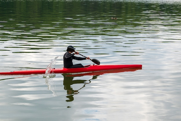 El hombre nada en un kayak rojo en un estanque