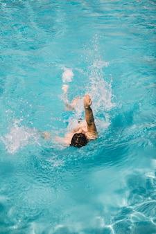 Hombre nadando braza de espalda en agua