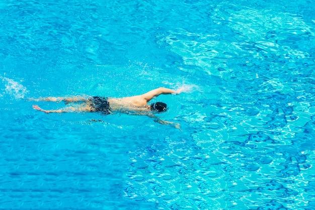 Hombre nadando en la piscina vista desde arriba