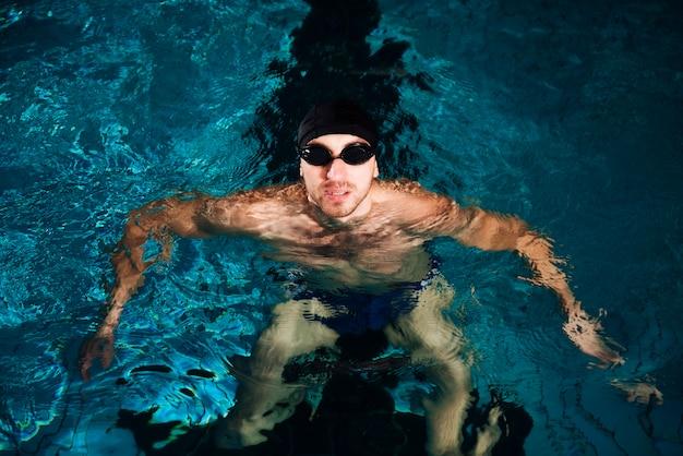 Hombre de natación de alto ángulo en cuenca
