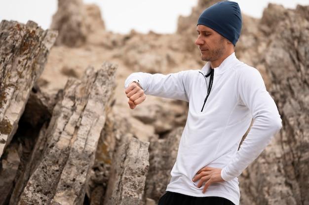 Hombre en la naturaleza mirando el reloj cerca de las rocas