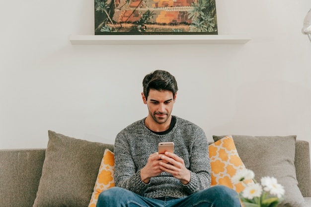 Hombre navegación por teléfono inteligente en la sala de estar
