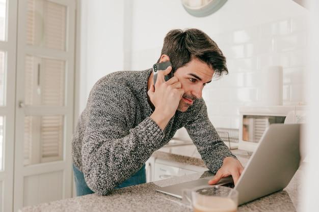 Hombre navegando portátil y hablando por teléfono