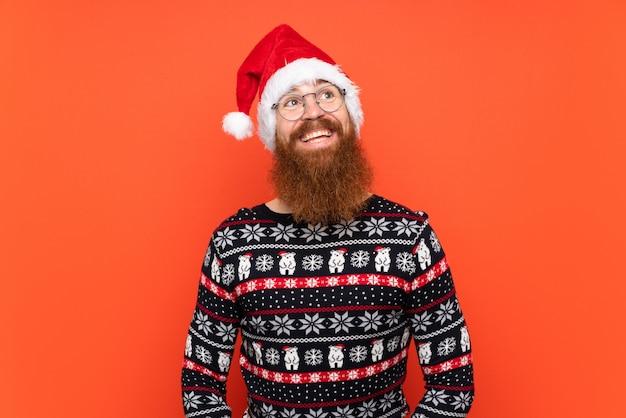Hombre de navidad con barba larga sobre fondo rojo aislado mirando hacia arriba mientras sonríe