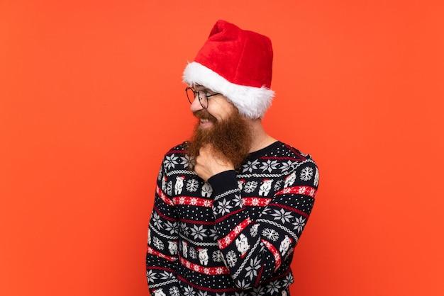 Hombre de navidad con barba larga sobre fondo rojo aislado mirando hacia el lado