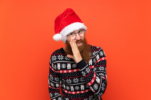 Hombre de navidad con barba larga sobre fondo rojo aislado susurrando algo