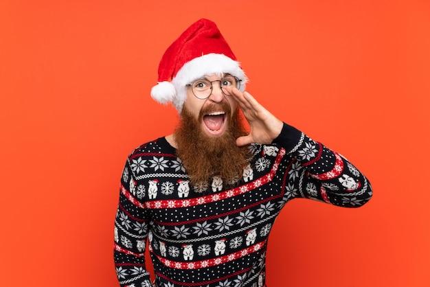 Hombre de navidad con barba larga sobre pared roja aislada gritando con la boca abierta