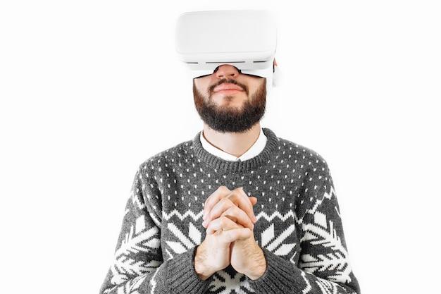 Hombre navidad en gafas d gafas de realidad virtual en el estudio sobre un fondo blanco.