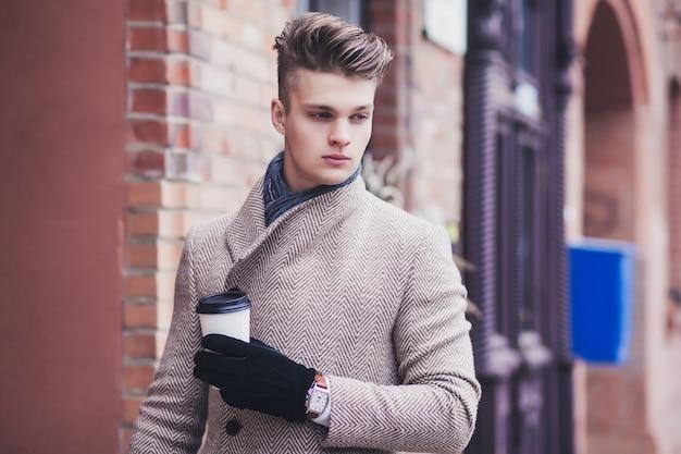 Hombre de negocios en abrigo bien arreglado disfrutar de coffee break urbano al aire libre