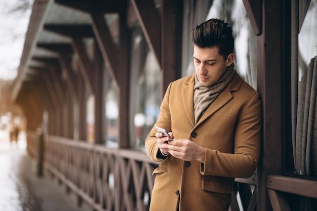 Hombre de negocios en abrigo hablando por teléfono afuera