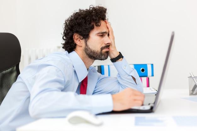 Hombre de negocios aburrido que trabaja en su computadora portátil