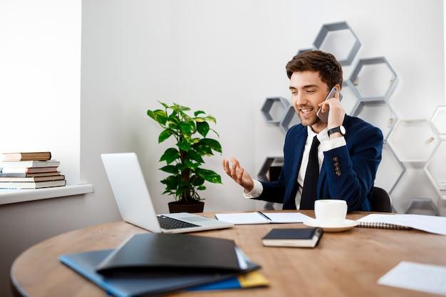 Hombre de negocios acertado joven que habla en el teléfono, fondo de la oficina.