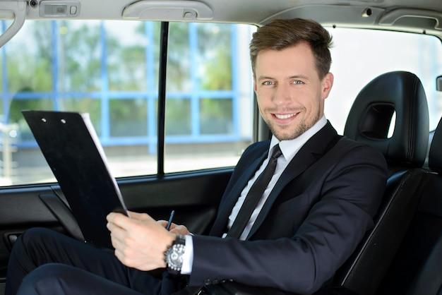 Hombre de negocios acertado joven que monta y sonrisa.