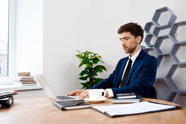 Hombre de negocios acertado joven que se sienta en la computadora portátil, fondo de la oficina.