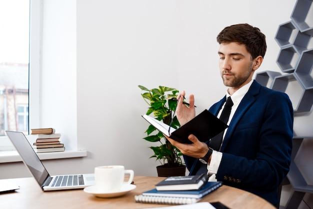Hombre de negocios acertado joven que se sienta en el lugar de trabajo, fondo de la oficina.