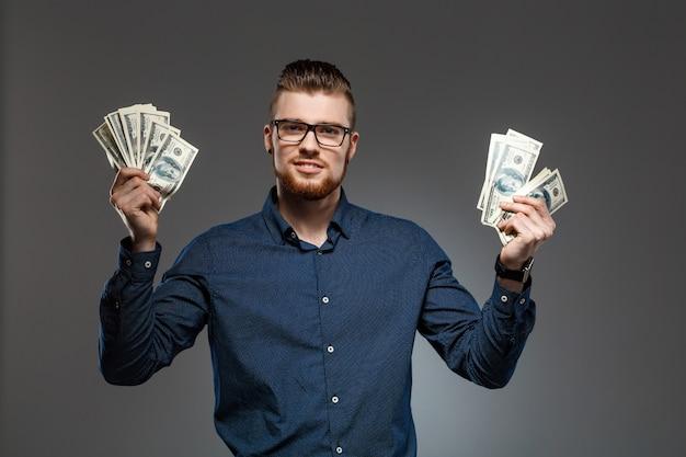 Hombre de negocios acertado joven que sostiene el dinero sobre la pared oscura.