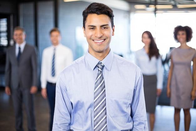 Hombre de negocios acertado que sonríe mientras que sus colegas que se colocan detrás de él en oficina