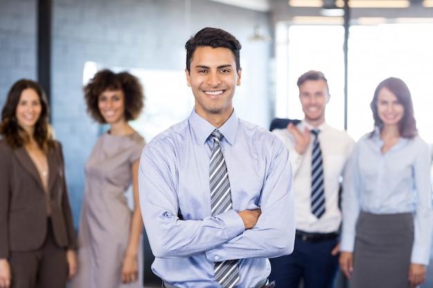 Hombre de negocios acertado que sonríe con sus brazos cruzados y sus colegas que presentan
