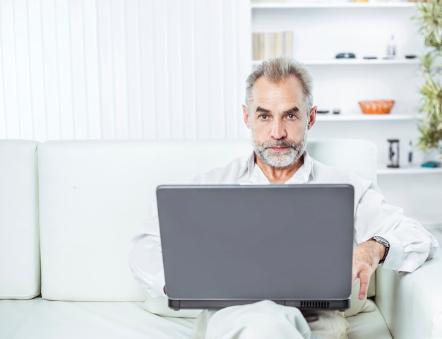Hombre de negocios acertado que trabaja en la computadora portátil que se sienta en el sofá en la oficina moderna