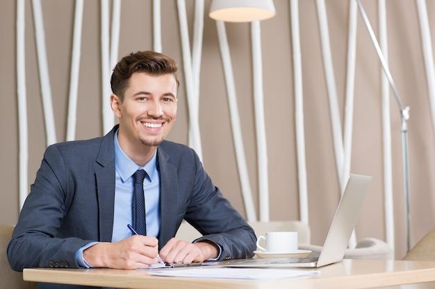 El hombre de negocios adulto feliz que trabaja en el escritorio en la oficina