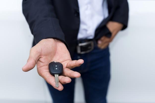 Hombre de negocios adulto masculino en un traje y sosteniendo una llave del coche en su mano. coches blancos al fondo.