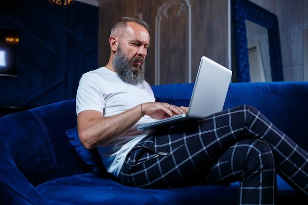 Hombre de negocios adulto, profesor, mentor trabajando en un nuevo proyecto. se sienta junto a una gran ventana sobre la mesa. mira la pantalla del portátil.
