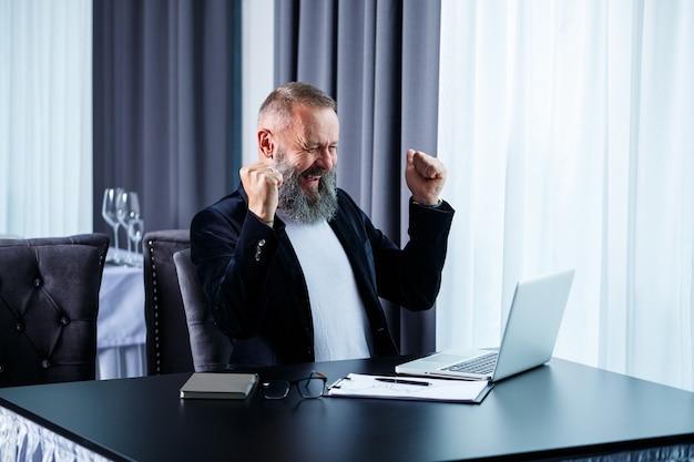 Un hombre de negocios adulto está trabajando en un nuevo proyecto y está mirando las tablas de crecimiento de las acciones. se sienta a la mesa junto a la ventana grande. mira la pantalla del portátil y sonríe