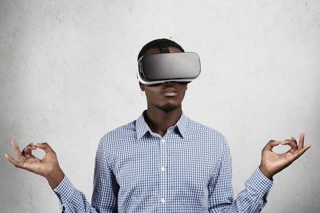 Hombre de negocios africano en camisa a cuadros azul y auriculares 3d, jugando videojuegos en la oficina.
