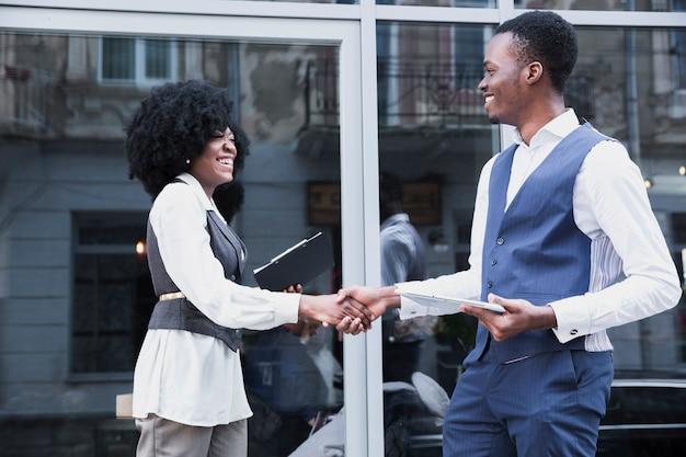Hombre de negocios africano joven y hombre de negocios que sacuden la mano delante de la ventana de cristal