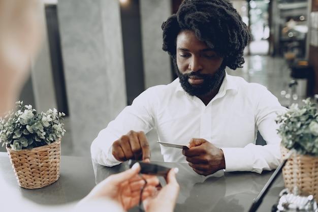 Hombre de negocios africano pagando la estancia en el hotel con tarjeta de crédito