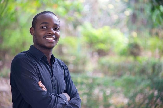 Hombre de negocios africano que mira y que sonríe en naturaleza verde.