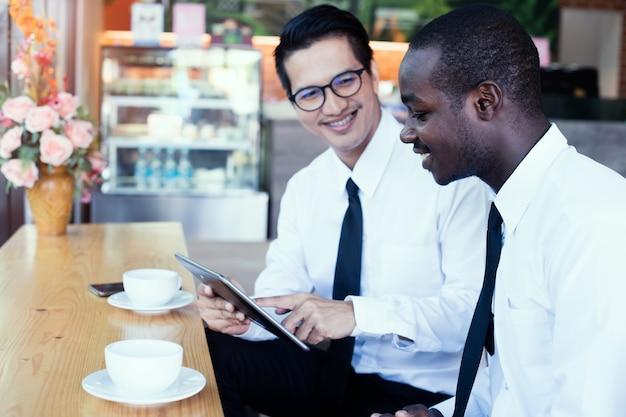 Hombre de negocios africano que mira la tableta con los amigos asiáticos