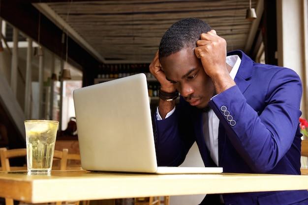 Hombre de negocios africano que se sienta con la computadora portátil en el café