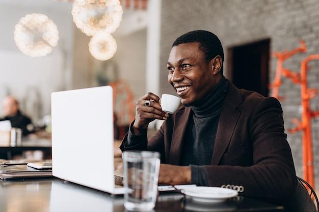 Hombre de negocios africano que usa el teléfono y que bebe café mientras que trabaja en la computadora portátil en un restaurante.