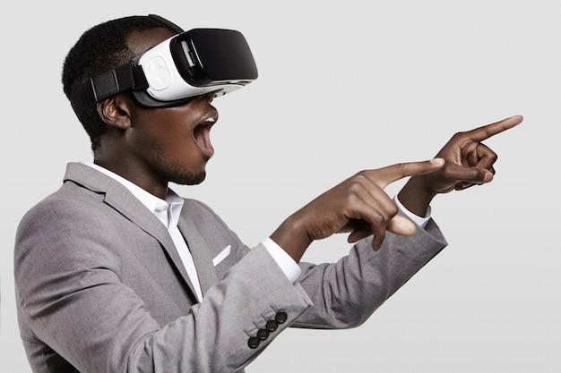 Hombre de negocios africano sorprendido que usa auriculares oculus rift, experimentando la realidad virtual mientras juega videojuegos.