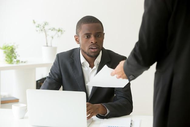 Hombre de negocios africano sorprendido sorprendido que recibe un aviso inesperado de un colega caucásico