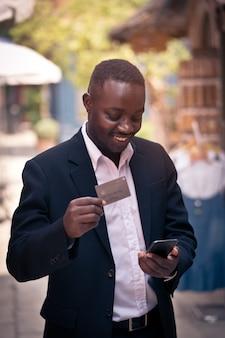 Hombre de negocios africano usando un pago con tarjeta de crédito comprando en línea en su teléfono inteligente