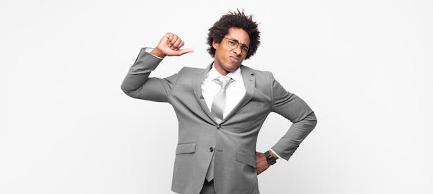 Hombre de negocios afro negro sintiéndose serio, fuerte y rebelde, levantando el puño, protestando o luchando por la revolución