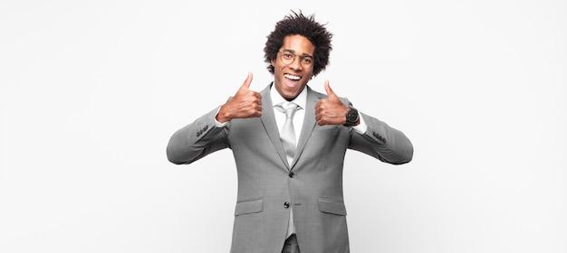 Hombre de negocios afro negro sonriendo ampliamente luciendo feliz, positivo, seguro y exitoso, con ambos pulgares hacia arriba