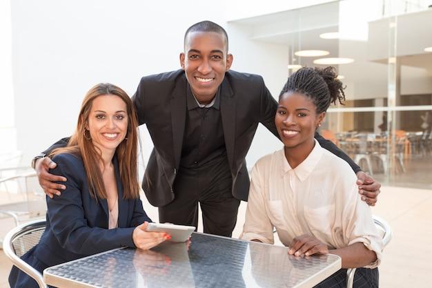 Hombre de negocios afroamericano feliz que abraza a colegas femeninos