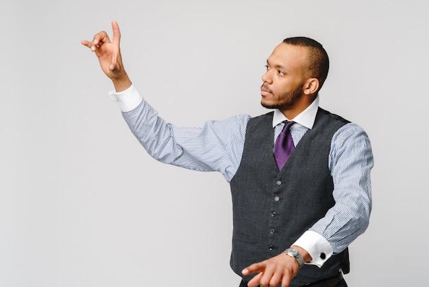 Hombre de negocios afroamericano joven hermoso que señala su dedo a la pantalla virtual.