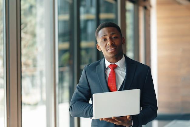 Hombre de negocios afroamericano joven hermoso en el traje clásico que sostiene un ordenador portátil y una sonrisa