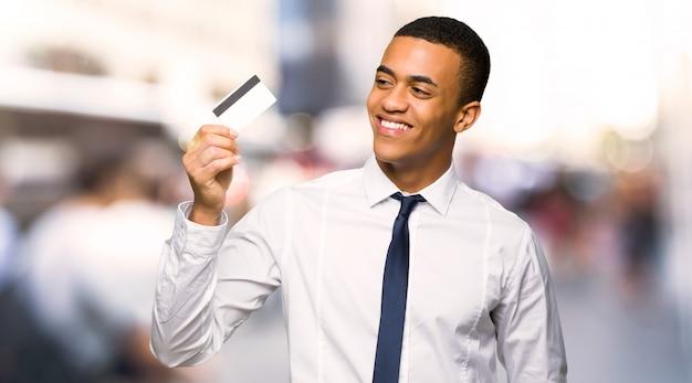 Hombre de negocios afroamericano joven que sostiene una tarjeta de crédito y que piensa en la ciudad