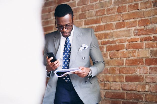 Hombre de negocios afroamericano con revista y teléfono