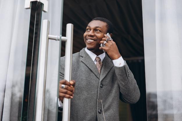 Hombre de negocios afroamericano en traje gris clásico al salir del edificio de oficinas
