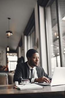 Hombre de negocios afroamericano usando una computadora portátil en un café.