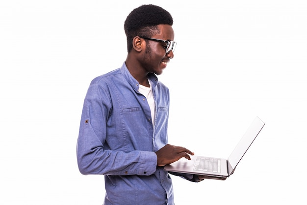 Hombre de negocios afroamericano usando una computadora portátil y posando aislado sobre pared blanca