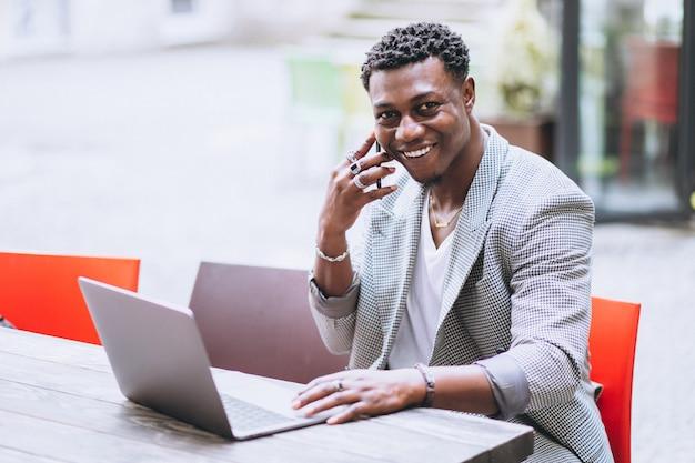 Hombre de negocios afroamericano usando laptop en un café