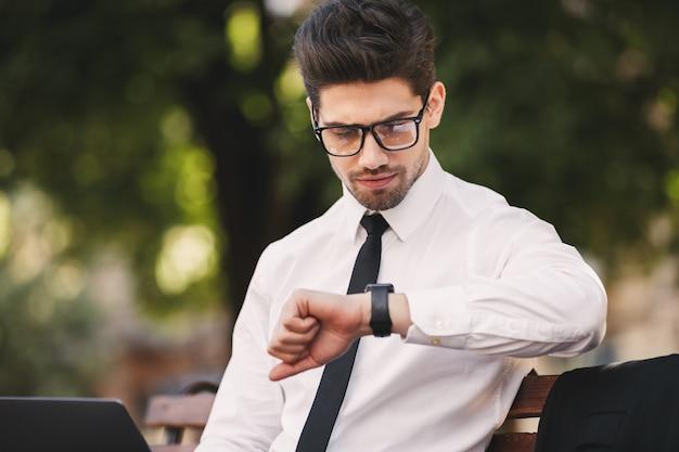 Hombre de negocios al aire libre en el parque mirando el reloj.
